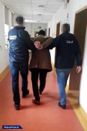 Dwaj policjanci prowadzą podejrzanego