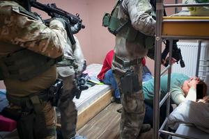 policjanci CBŚP pilnują osób zatrzymanych