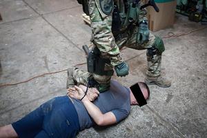 Policjant CBŚP pilnuje osoby zatrzymanej