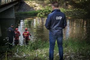 """Policjant w kurtce z napisem """"CBŚP"""", w tle strażacy wchodzący do rzeki."""