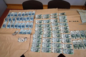 Liczne banknoty o nominale 50 i 100 PLN leżące na blacie stołu.