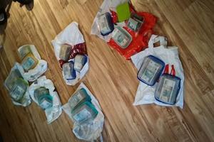 Kilkanaście plastikowych pudełek wypełnionych plikami banknotów o nominale m.in. 100 PLN leżących na podłodze.